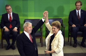 Brasília - Presidente Dilma Rousseff durante cerimônia de posse dos novos ministros ergue o braço em sinal de vitória do novo ministro da Casa Civil, Luiz Inácio Lula da Silva. Foto: José Cruz / Agência Brasil