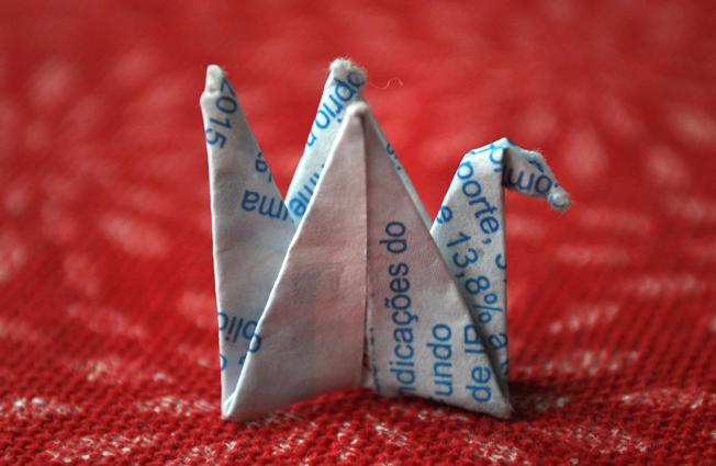 Origami que representa a ave Grou, feito pelo Zé Carlos, entre os solavancos do caminho na distância das ruas Azevedo Soares e Euclides Pacheco. O Grou ou Tsuru (em japonês) é uma ave sagrada do Japão. Símbolo da saúde, também traz boa sorte, felicidade, longevidade e fortuna. Foto: aloimage