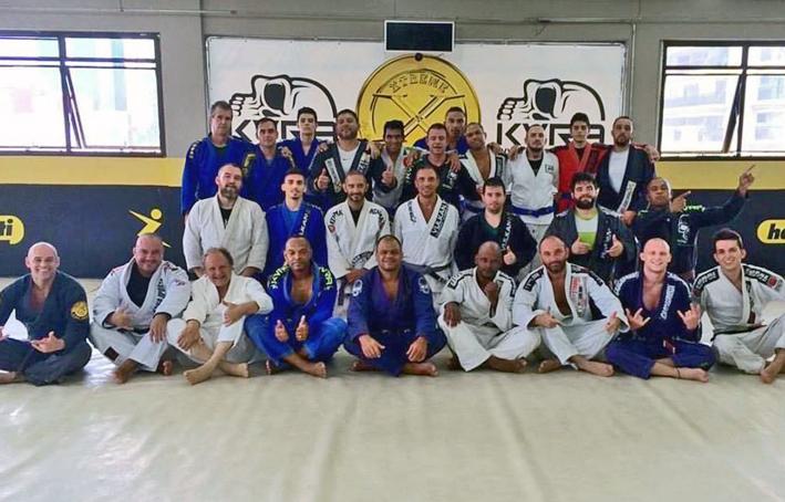 Mestre Pedra (sentado, no centro da foto)  com seus alunos no final do treino da manhã. Em pé Guilherme (3º da esquerda para a direita) e Chapolim (com kimono vermelho) ao lado dos colegas que os incentivam diariamente. Foto: divulgação