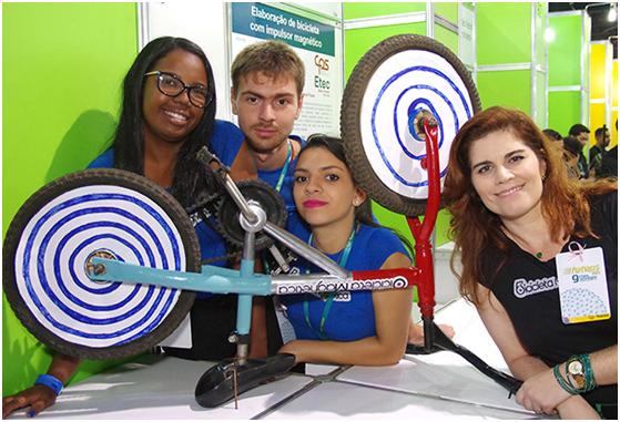 Alunos Kauana Meireles, Gabriel Souza e Ingrid Fauzie durante exposição do protótipo da bicicleta magnética na Feteps 2015, ao lado da orientadora, Maíra Cezaretto. Foto: Gastão Guedes