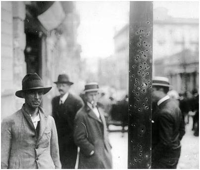 Transeuntes perto de poste atingido por balas de fuzil, durante a Revolução de 1924. Foto: Acervo FES