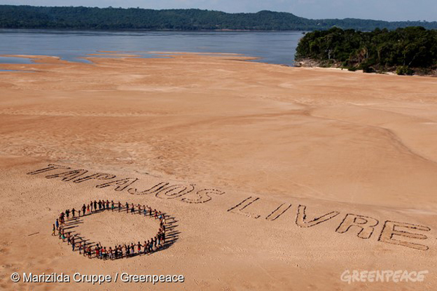 "Ativistas do Greenpeace e índios Munduruku usam pedras para formar a frase ""Tapajós Livre"" nas areias de uma praia às margens do rio de mesmo nome, próximo ao município de Itaituba, no Pará. O protesto, que contou com a participação de cerca de 60 Munduruku, ocorreu na região onde o governo pretende construir a primeira de uma série de cinco hidrelétricas na bacia do Tapajós. Itaituba, Pará. 26/11/2014.  Greenpeace activists and the Munduruku indigenous people use stones to form the ""Tapajós Free"" phrase on a sandy beach on the banks of the eponymous river, near the city of Itaituba, in Pará, Brazil. The protest, attended by about 60 Munduruku, occurred in the region where the government plans to build the first of a series of five dams in the Tapajós basin. Foto: Marizilda Cruppe/Greenpeace."